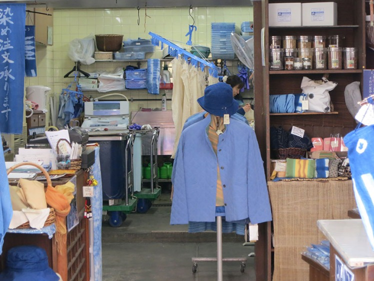 The shop with do-it-yourself dyeing has a few racks of clothes on the sidewalk, and looks like this when you peek through the doorway.