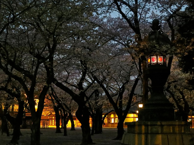 A stone lantern glows in the twilight, with the buildings of the main shrine beyond.
