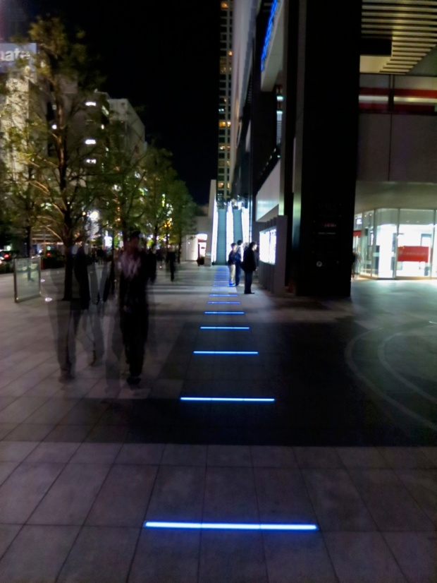 On the corner near the UDX building, a mysterious path of blue neon bars leads up up the stairs to the Anime Center, and beyond.
