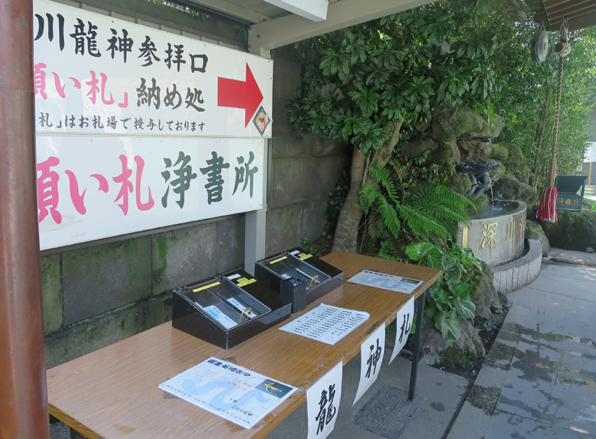 The table for buying paper and writing wishes is to the left of the fountain.