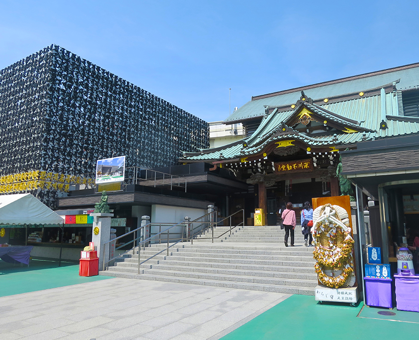 Fire Ceremonies are held in the traditional temple building to the right; the hall of 10,000 fudo figures is in the modern building to the left. The characters on the outside are Sanskrit, and they spell out the Fudo Sutra.