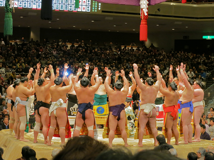 Sumo wrestlers saluting each other in circle before a tournament