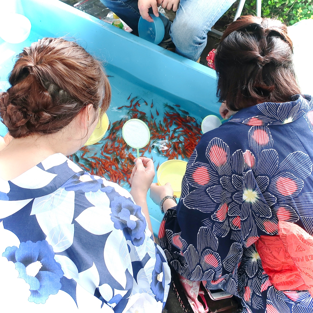 Two young women in yukata catching goldfish